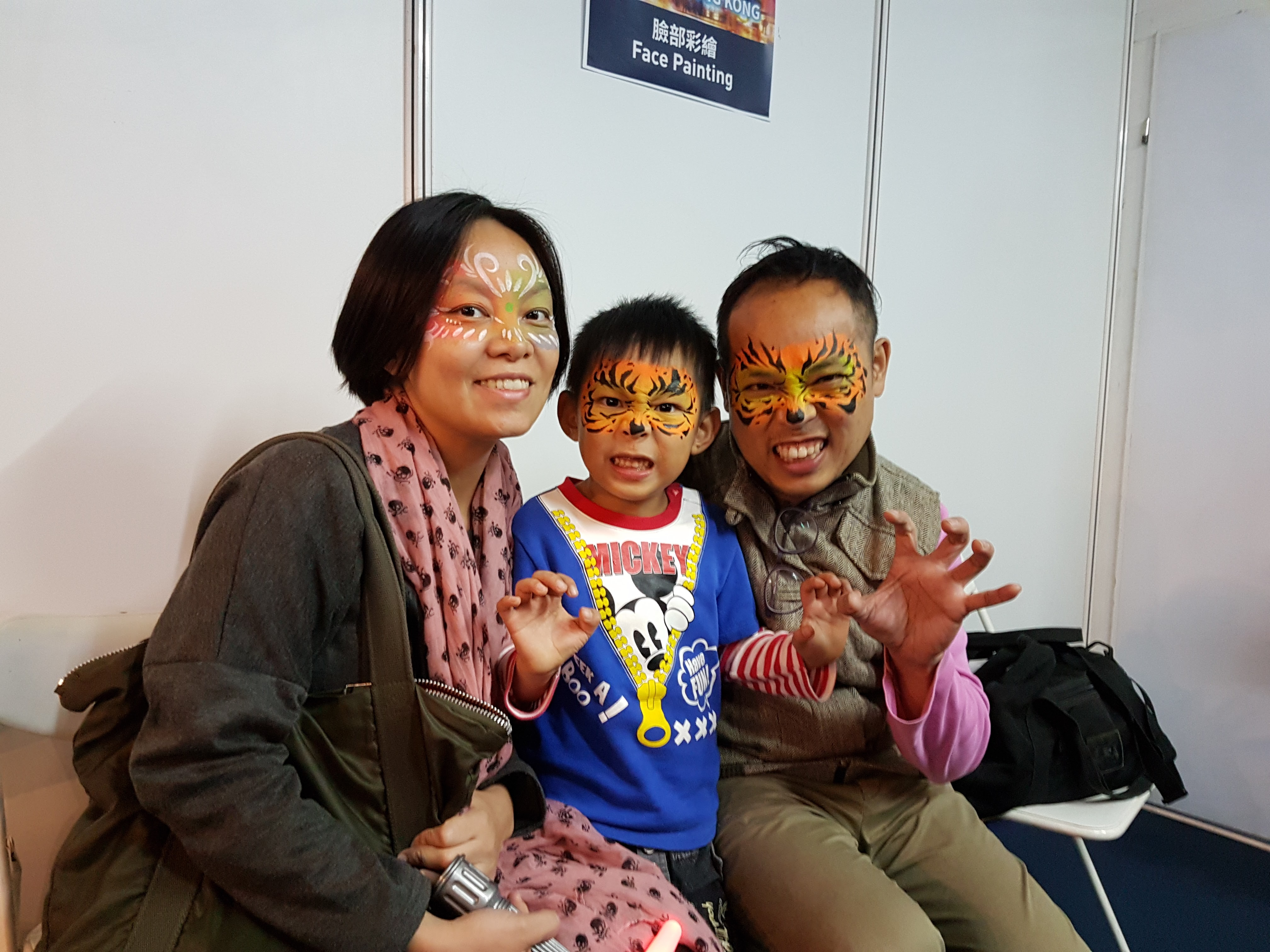 A family positing at the free face painting booth at Lumieres Hong kong